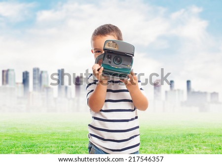 portrait of a little boy taking photos with  camera - stock photo