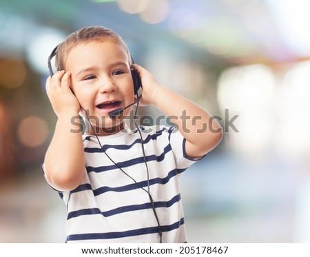 portrait of a little boy talking by headset - stock photo