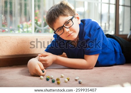 Portrait of a little boy with glasses lying on the carpet floor and playing with some marbles at home - stock photo