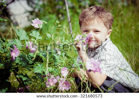 portrait of a little boy with wildflowers in park at the day time - stock photo