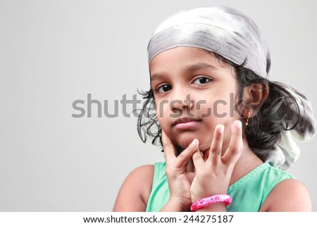 Portrait of a little girl a fashion cloth tied over head - stock photo
