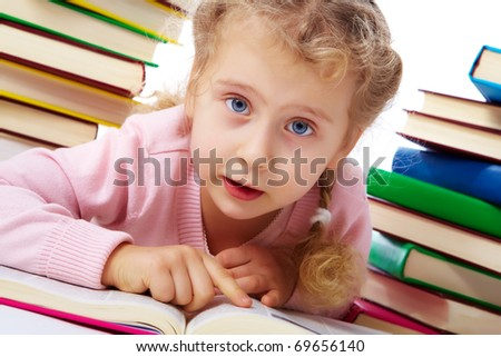 Portrait of a little girl among books - stock photo