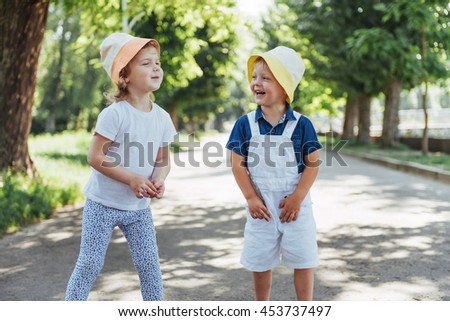 portrait of a little girl and her brother. Children playing outdoors on a sunny summer day. Family holidays. - stock photo