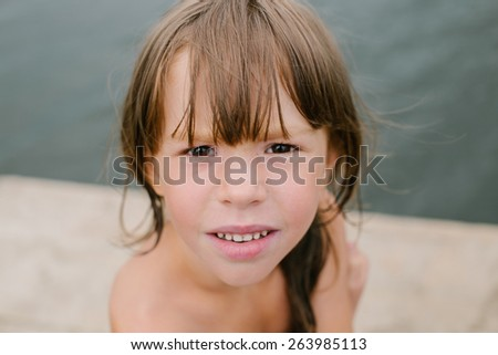 Portrait of a little girl at the beach on hot summer day. Having fun during vacation. Girl playing on wooden deck at the lake - stock photo