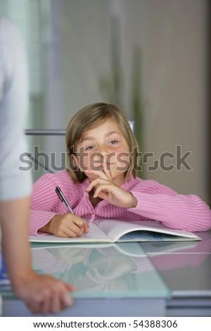 Portrait of a little girl doing homework - stock photo