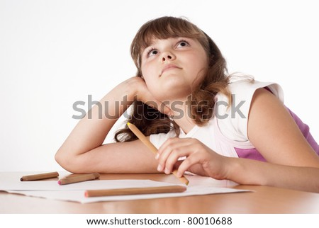 portrait of a little girl drawing at table - stock photo