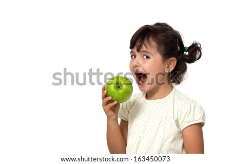 portrait of a little girl eating apple isolated on white - stock photo