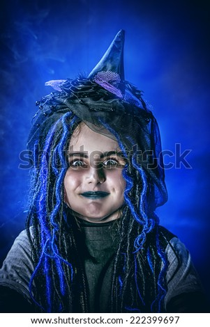 Portrait of a little girl in a costume of witch posing over dark background. - stock photo