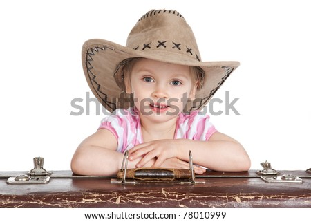 Portrait of a little girl in a cowboy hat with a suitcase over white - stock photo