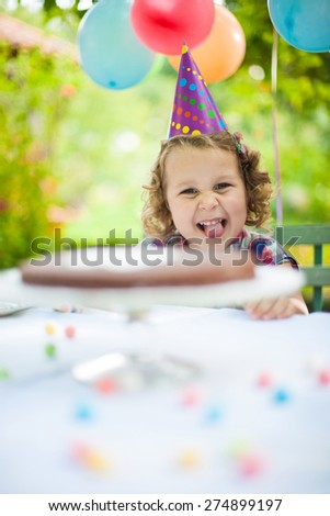 portrait of a little girl in a garden party for her birthday, she wears a funny hat and the garden  is decorated with balloons - stock photo