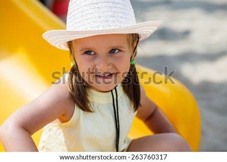 Portrait of a little girl in a white hat and a yellow t-shirt on a clear sunny day. Shallow depth of field. Focus on the model's face. - stock photo