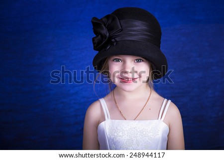 Portrait of a little girl in an elegant hat on a blue background - stock photo