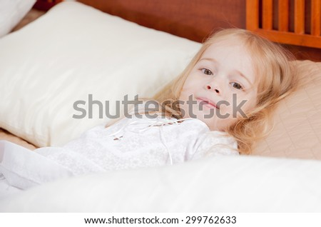 portrait of a little girl in bed - stock photo