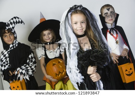 Portrait of a little girl in Halloween outfit with friends holding pumpkin in the background - stock photo