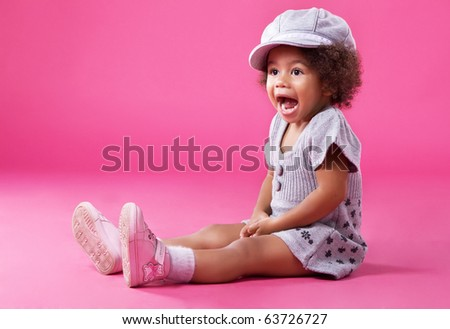 Portrait of a little girl in stylish clothing sitting on pink background and playing up - stock photo