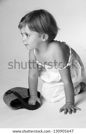Portrait of a little girl on her knees with a small bag. - stock photo