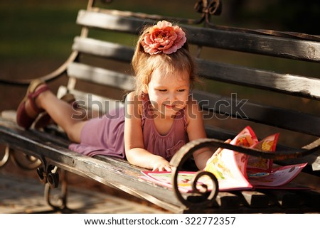 Portrait of a little girl reading a children's book on a park bench - stock photo