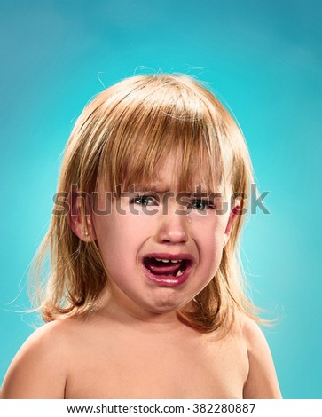 Portrait of a little girl. She is crying - stock photo