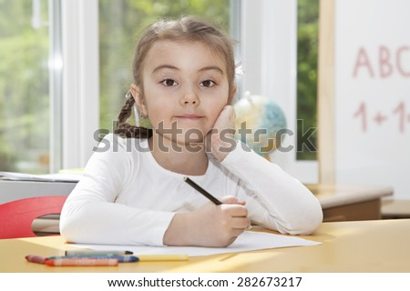Portrait of a little girl sitting at the table, looking at camera
