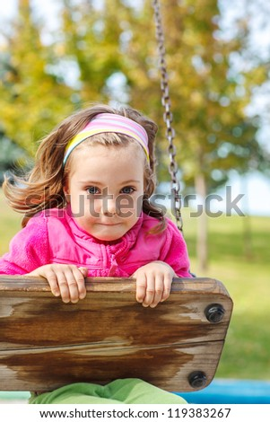 Portrait of a little girl swinging on the playground - stock photo