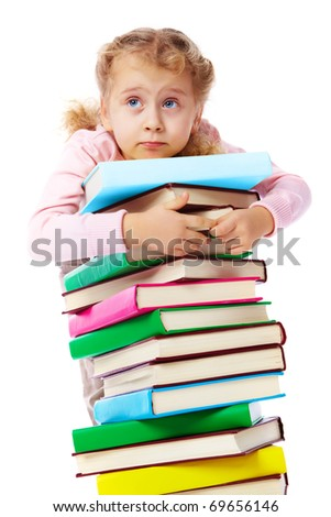 Portrait of a little girl trying to carry a huge heap of books - stock photo