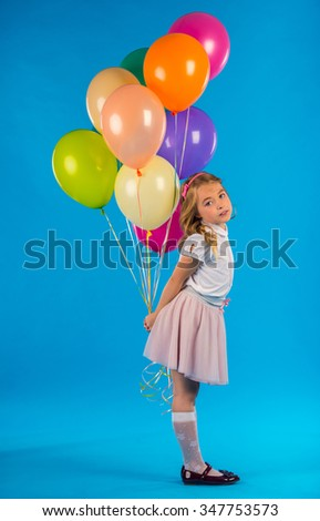 Portrait of a little girl with balloons isolated on blue background - stock photo