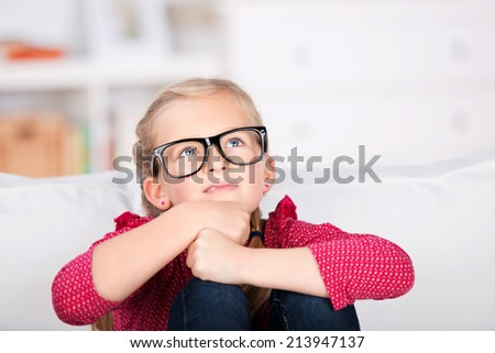 Portrait of a little girl with big glasses sitting on couch at home - stock photo