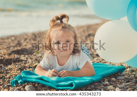 Portrait of a  little girl with blue air balloons on the beach. A nice little girl lying on the beach with blue  air balloons. - stock photo