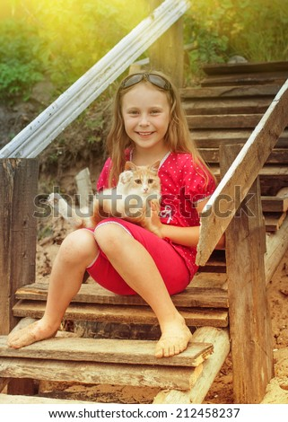 Portrait of a little girl with kitten in nature. - stock photo