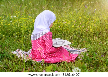 Portrait of a little girl with the quran in their hands - stock photo