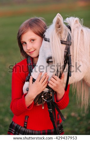 Portrait of a little young girl model hugs white horse's head and looking at the camera Outdoors - stock photo