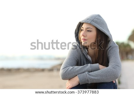 Portrait of a longing pensive teenager sitting on the beach looking away at the horizon in the morning - stock photo