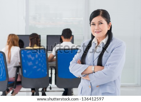 Portrait of a lovely college teacher with her students studying in the background - stock photo