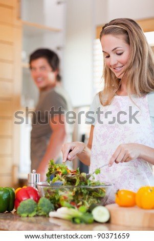 Portrait of a lovely couple making a salad in their kitchen - stock photo