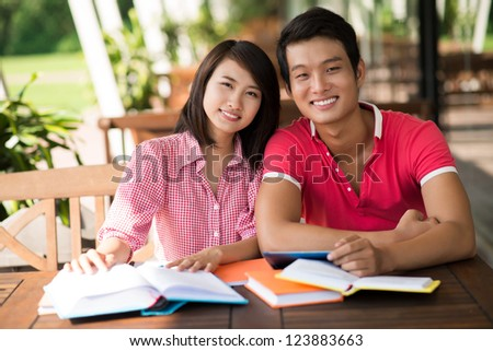 Portrait of a lovely couple studying together in a summerhouse - stock photo