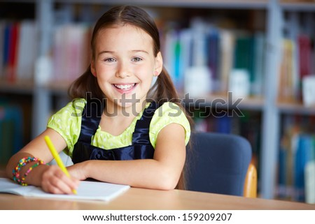 Portrait of a lovely girl sitting in library - stock photo