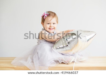 Portrait of a lovely little girl in elegant gray dress in front of a white background. Little princess. Little baby girl playing with silver star-shaped balloon. - stock photo