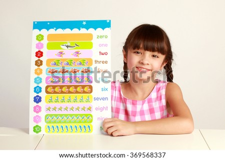 portrait of a lovely little girl, smiling, learning math, dressed in school uniform, isolated on white background - stock photo