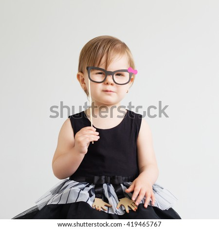 Portrait of a lovely little girl with funny photo props paper glasses against a white background - stock photo