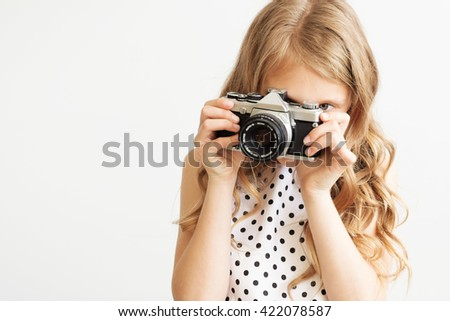 Portrait of a lovely little girl with old SLR film camera against a white background - stock photo