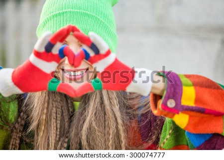 Portrait of a lovely woman autumn  woman, making heart symbol of fingers, focus on face - stock photo