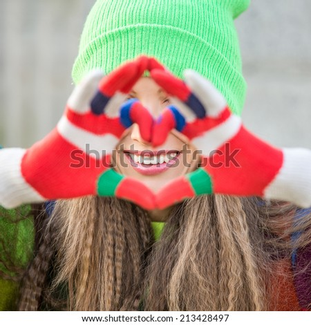 Portrait of a lovely woman making heart of fingers. focus on face - stock photo