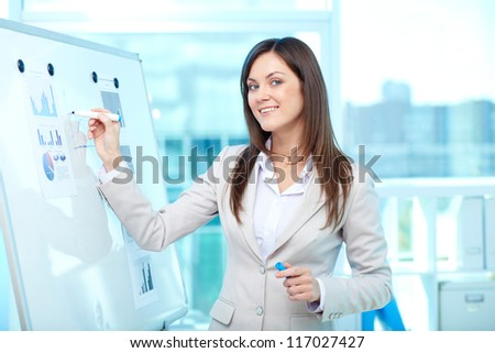 Portrait of a lovely young businesswoman presenting her project on board - stock photo
