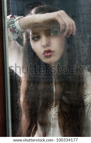 Portrait of a lovely young lady looking through glass window - Indoor in a dark cloudy day, she looks down at right and her head is resting on the right arm - stock photo