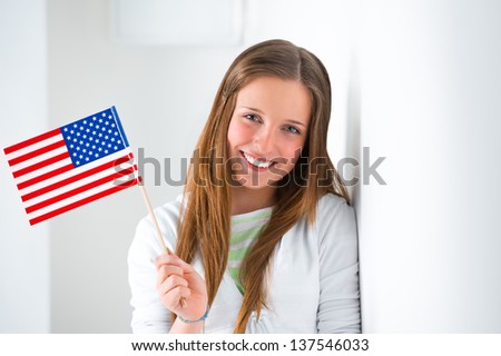 Portrait of a lovely young woman with United State's flag smiling - stock photo