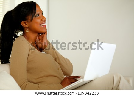 Portrait of a lovely young woman working on laptop while looking up and smiling - stock photo