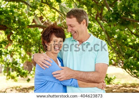 Portrait of a loving mature couple with their arms around each other laughing, with the husband looking lovingly at his wife - stock photo