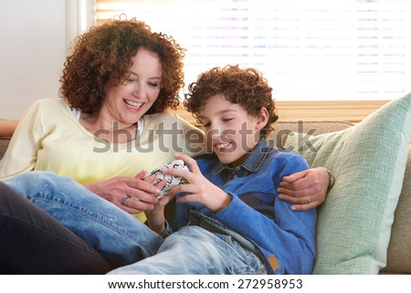 Portrait of a loving mother sitting with her son at home looking at game he is playing on mobile device - stock photo