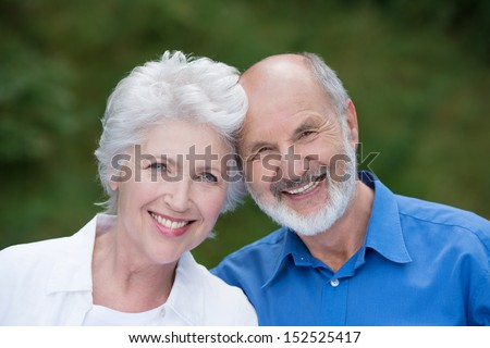 Portrait of a loving senior couple standing together outdoors facing the camera and smiling with their heads touching - stock photo