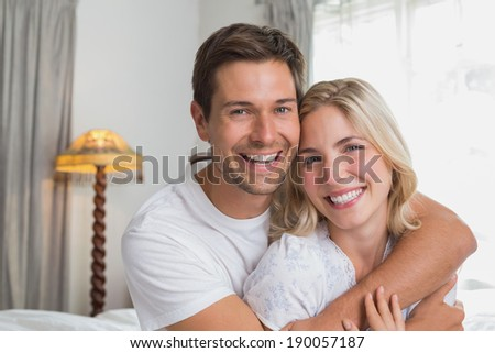 Portrait of a loving young man embracing woman from behind at home - stock photo